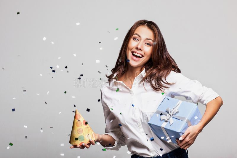 有礼物盒的美丽的愉快的妇女在与落到处在她的五彩纸屑的庆祝党 免版税库存照片