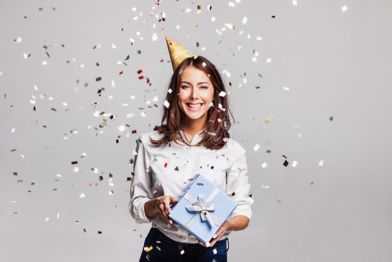 有礼物盒的美丽的愉快的妇女在与落到处在她的五彩纸屑的庆祝党 免版税库存图片