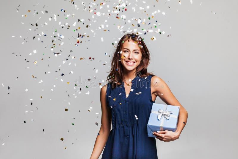 有礼物盒的美丽的愉快的妇女在与落到处在她的五彩纸屑的庆祝党 免版税图库摄影