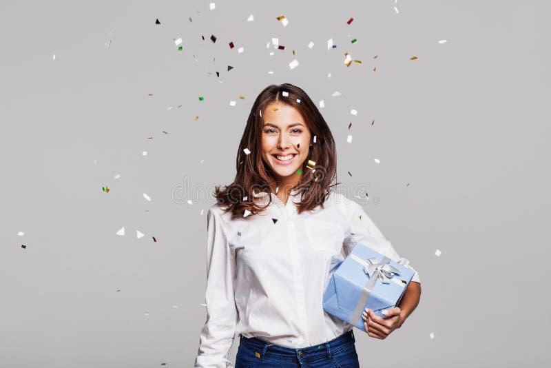 有礼物盒的美丽的愉快的妇女在与落到处在她的五彩纸屑的庆祝党 库存照片