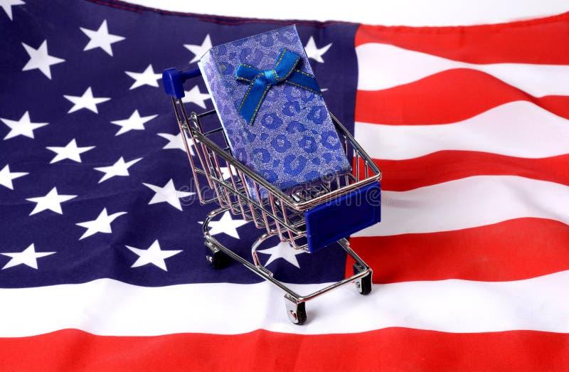 有礼物盒的购物车在美国旗子-自由交付 库存图片