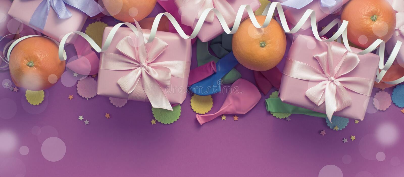 有礼物缎丝带的横幅装饰构成三箱子鞠躬桔子五彩纸屑蛇纹石生日聚会 免版税库存图片