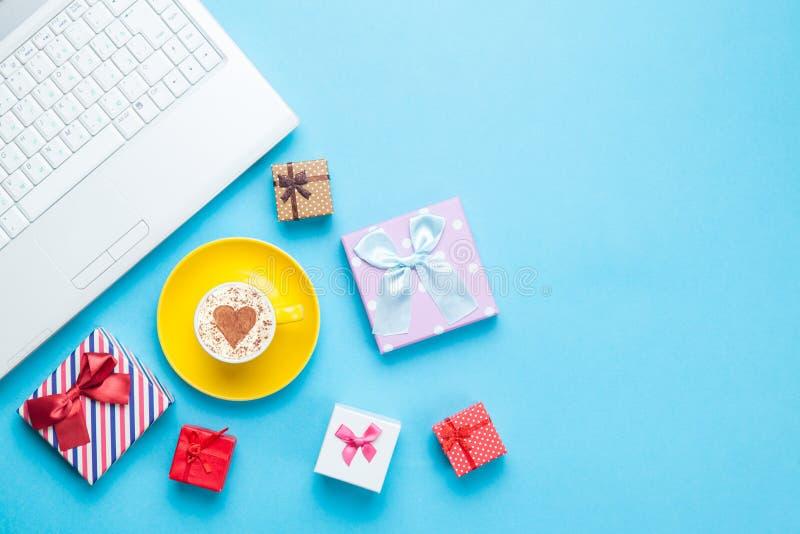 有礼物bxes和热奶咖啡的计算机 图库摄影