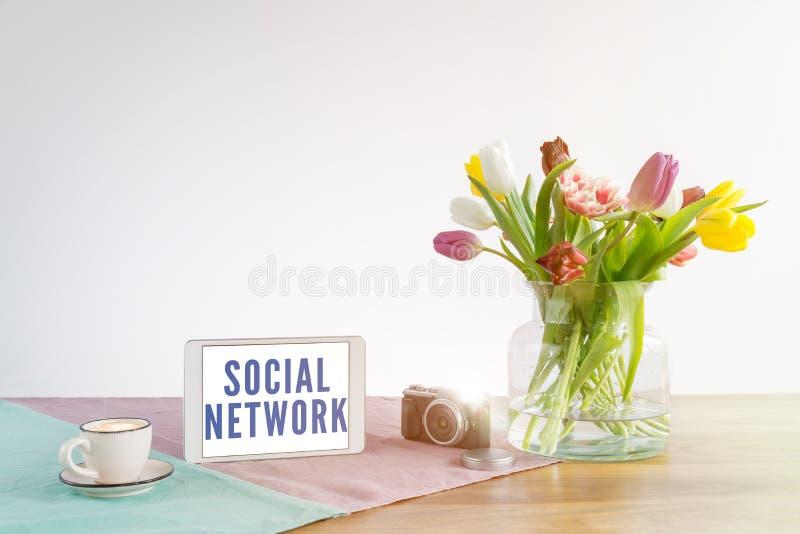 有社会网络文字的片剂在有白色bac的木书桌上 免版税库存照片
