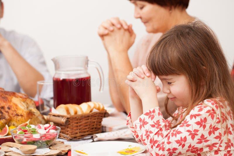 有祈祷在膳食前的家庭的小女孩 免版税库存图片