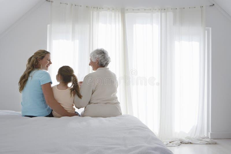 有祖母和母亲的女孩坐床 免版税库存图片