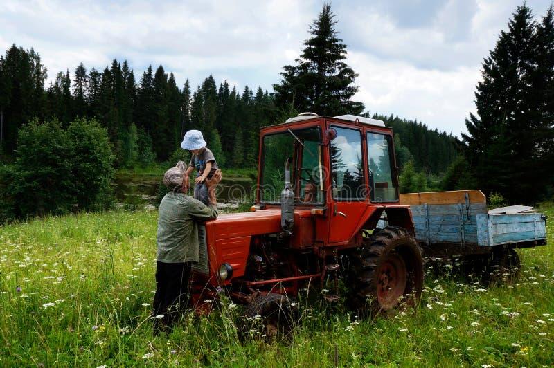 有祖父农夫的和一台拖拉机的孙子在草甸的森林里 免版税库存图片