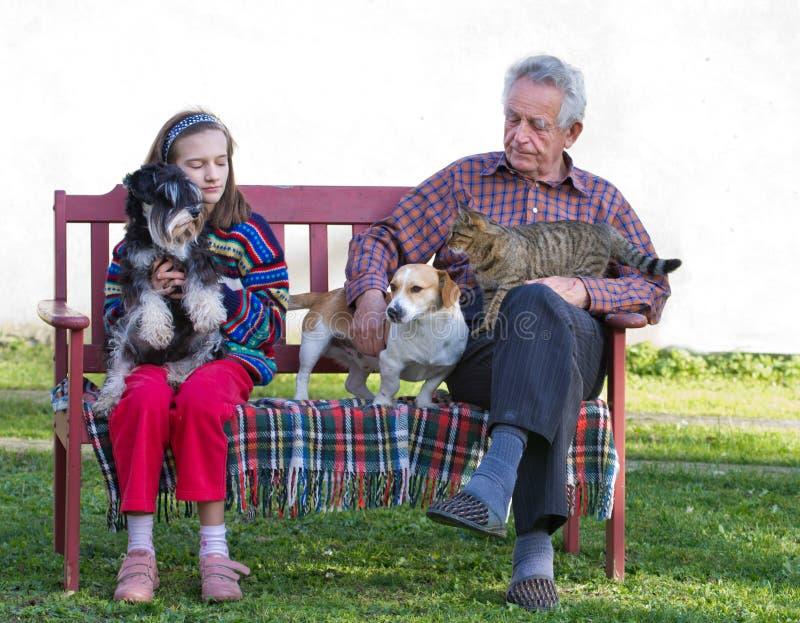 有祖父和宠物的女孩 免版税图库摄影