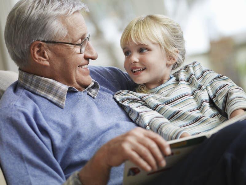 有祖父读书故事书的女孩 库存图片