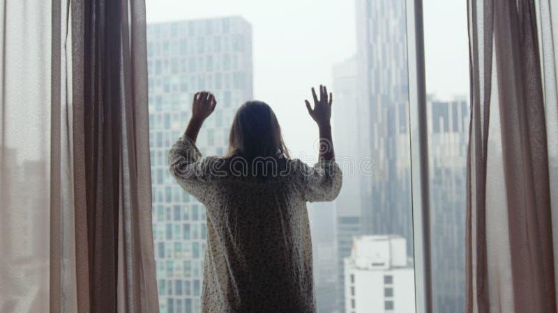 有神色的哀伤的女孩在curban建筑学的窗口里在雨期间 免版税库存图片