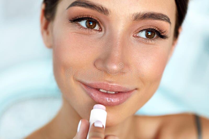 有秀丽面孔的美丽的妇女应用在嘴唇的香脂 应用关心皮肤透明油漆 库存图片