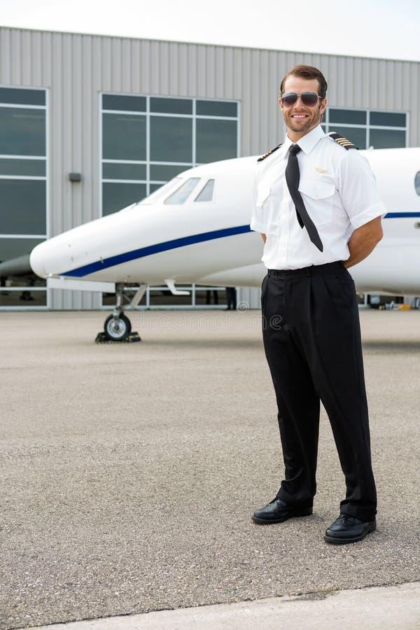 有私人喷气式飞机的确信的飞行员在背景中 库存照片