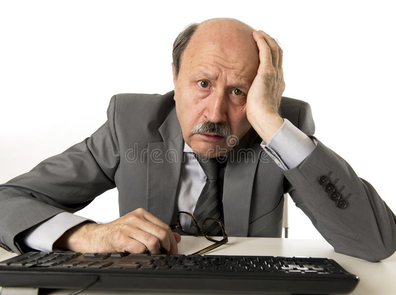 有秃头的商人在他的60s工作被注重和被挫败在办公计算机看起来膝上型计算机的书桌疲乏 免版税库存照片