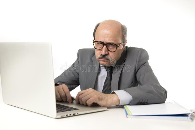 有秃头的资深成熟繁忙的商人在他的60s工作被注重和被挫败在办公计算机看a的膝上型计算机书桌 免版税图库摄影