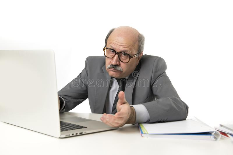 有秃头的资深成熟繁忙的商人在他的60s工作被注重和被挫败在办公计算机看a的膝上型计算机书桌 免版税库存照片