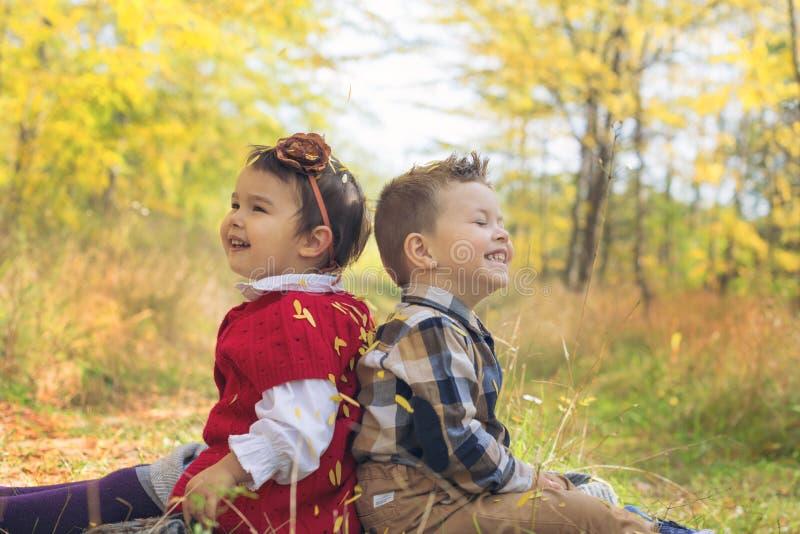 有秋叶的可爱的小孩在秀丽停放 免版税库存照片