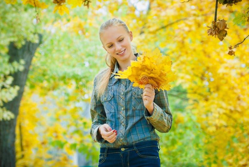 有秋叶的少妇 免版税库存图片