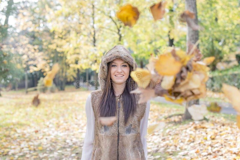 有秋叶的微笑的女孩在公园 免版税库存图片