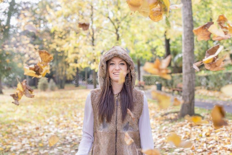 有秋叶的微笑的女孩在公园 库存图片