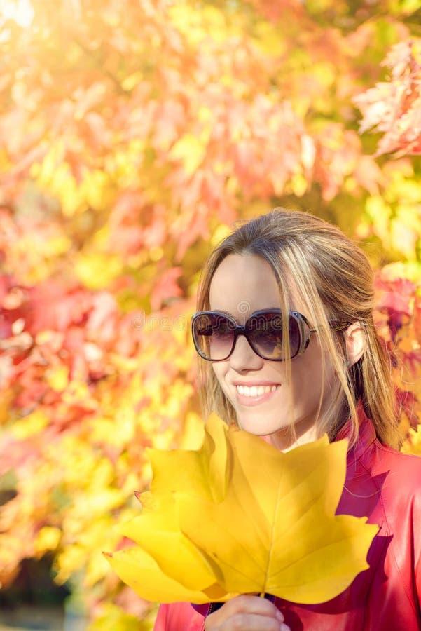 有秋叶的快乐的妇女在她的手上 免版税图库摄影