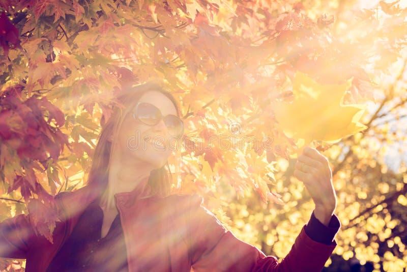有秋叶的快乐的妇女 库存照片