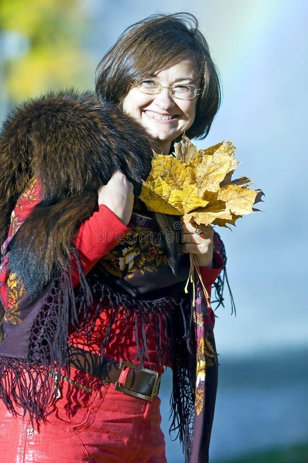 有秋叶的愉快的俏丽的夫人 免版税图库摄影