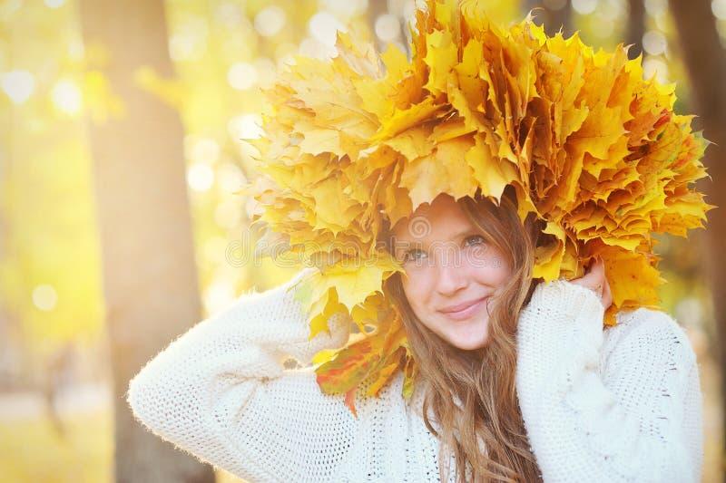 有秋叶的年轻美丽的女孩在他的手上 库存图片