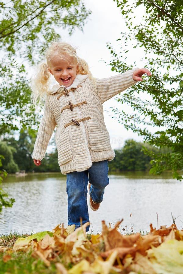 有秋叶的兴高采烈的小女孩 库存照片