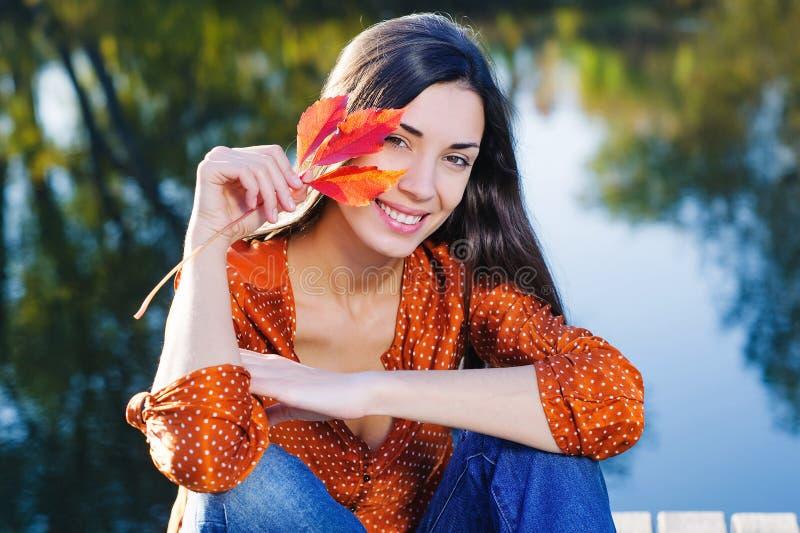 有秋天叶子的愉快的妇女 库存图片