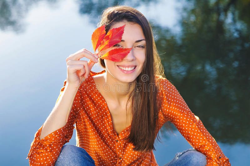 有秋天叶子的愉快的妇女 免版税库存照片