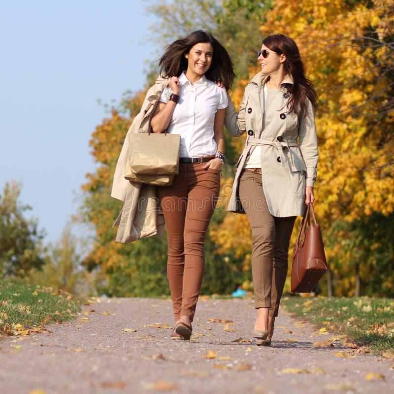 有秋天槭树的两名可爱的妇女在公园离开在秋天ou 免版税库存图片