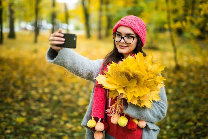 有秋天的快乐的少妇在前面制造的selfie生叶 库存照片
