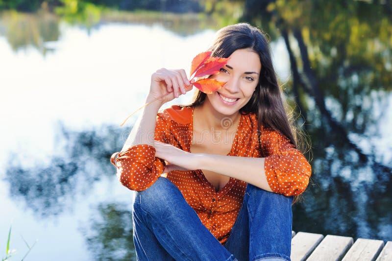 有秋天红色叶子的美丽的微笑的少妇 免版税库存照片