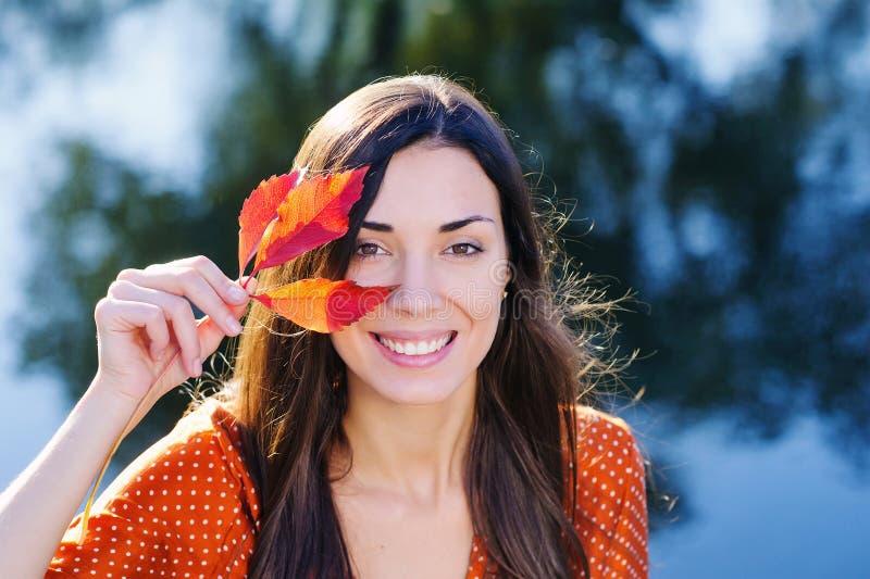 有秋天红色叶子的美丽的微笑的少妇 免版税库存图片
