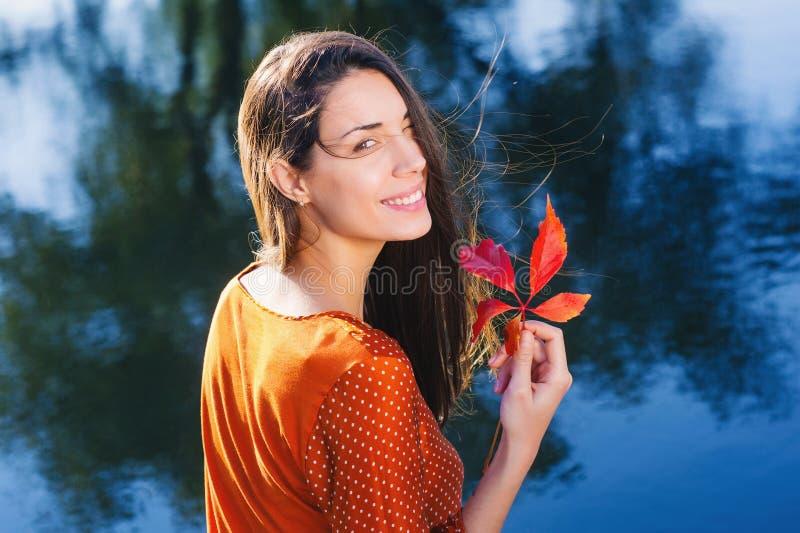 有秋天红色叶子的美丽的微笑的少妇 库存图片