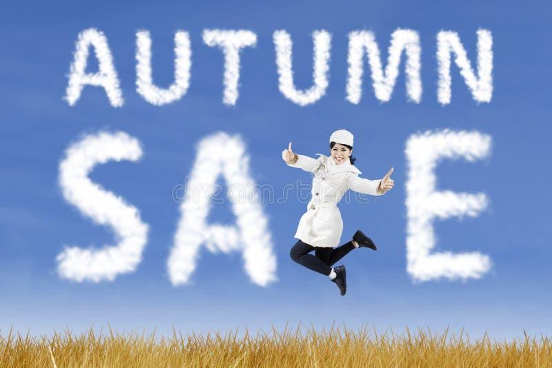有秋天销售标志的愉快的少妇 免版税图库摄影