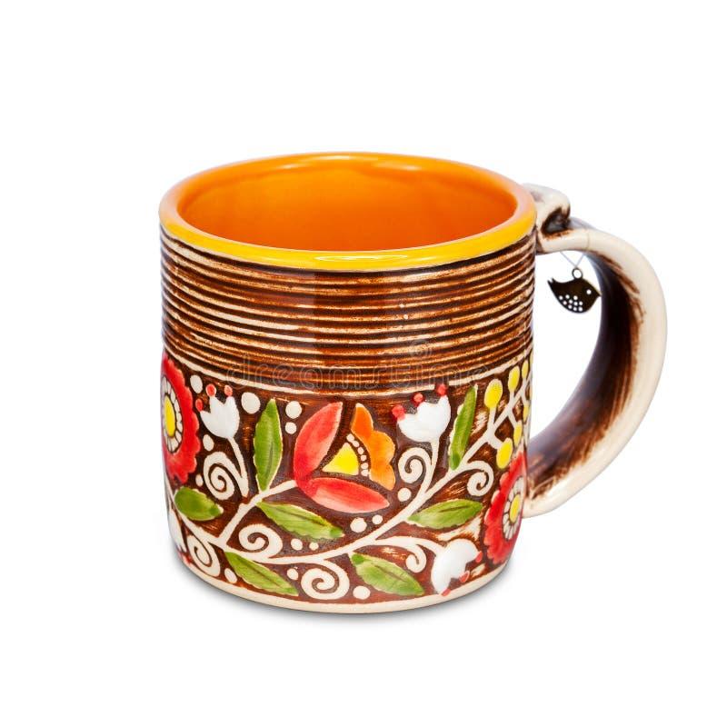 有种族花饰的橙色杯子在白色背景 库存照片