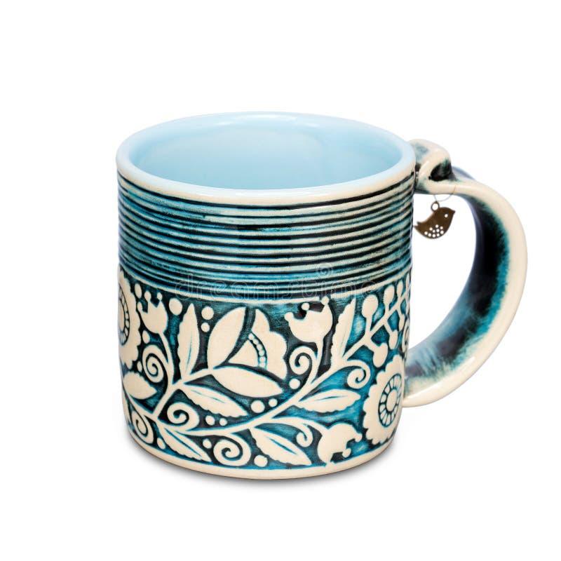 有种族花饰的蓝色杯子在白色背景 库存照片