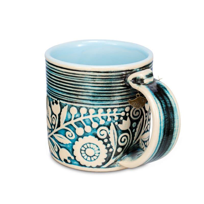 有种族花饰的蓝色杯子在白色背景 图库摄影