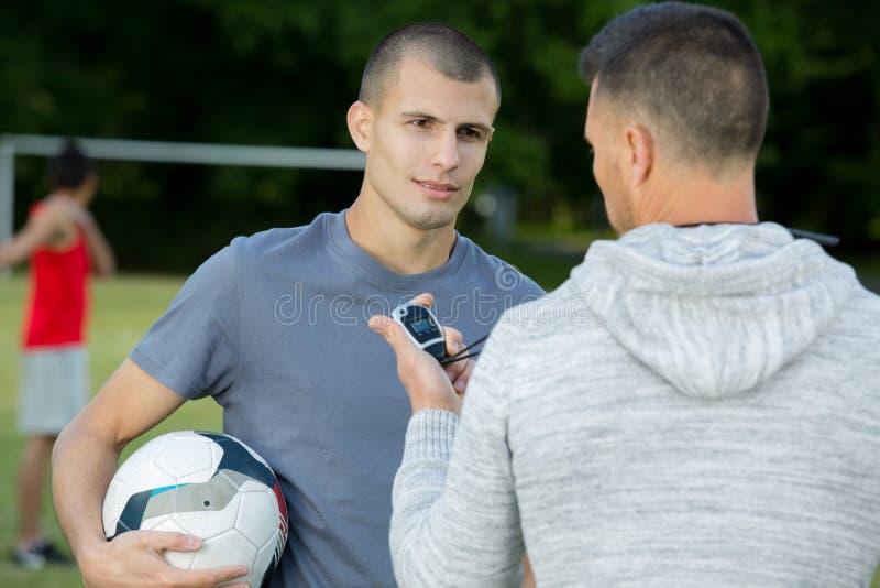 有秒表的教练谈话与年轻男性球员 免版税库存照片