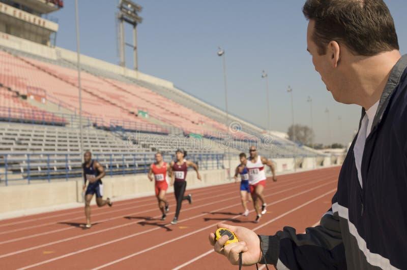 有秒表的教练,当赛跑在跑马场时的运动员 免版税库存图片