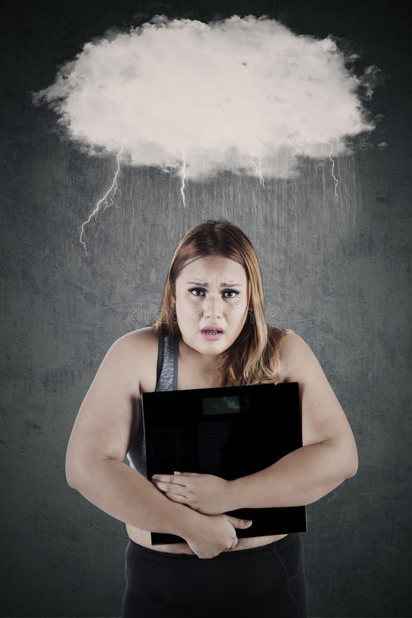 有秤的沮丧的妇女 免版税库存照片