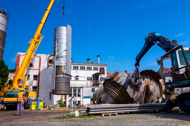 有移动式起重机的抓爪机器是放下大老金属坦克 免版税库存照片