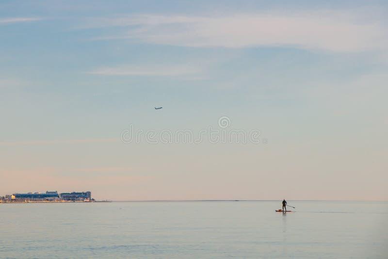 有移动横跨一个冲浪板的海的袋子的一个孤立人有桨的 r 免版税库存图片