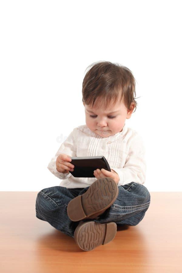 有移动电话的偶然婴孩 库存图片