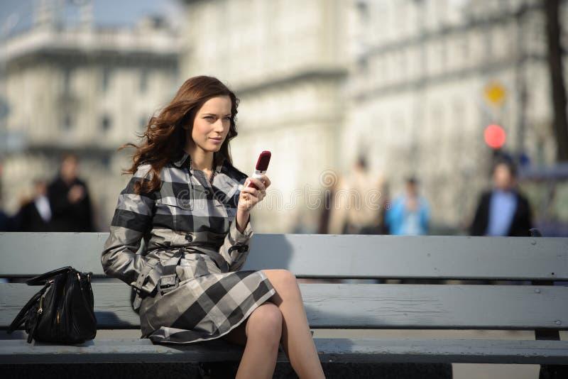 有移动电话的妇女在城市背景 免版税库存照片