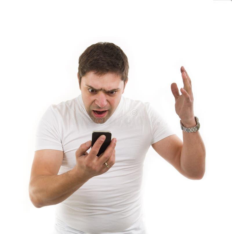 有移动电话的恼怒的年轻人 免版税库存图片