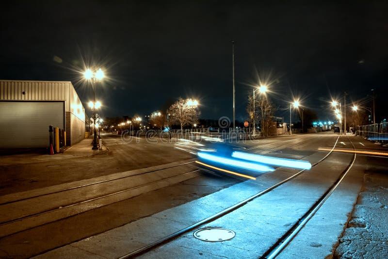 有移动的汽车和火车轨道的路在晚上 库存图片
