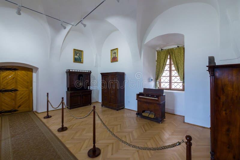 有稀有木家具、画象和一个窗口的白色博物馆展览室与一幅绿色帷幕 库存照片