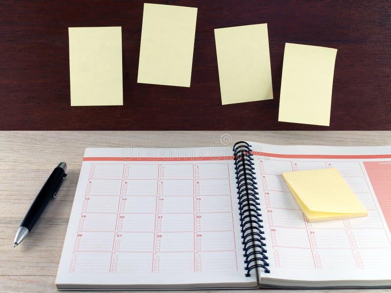 有稠粘的笔记和黑圆珠笔的开放笔记本在木桌上和关于黑褐色木墙壁的黄色空白的笔记 免版税库存照片